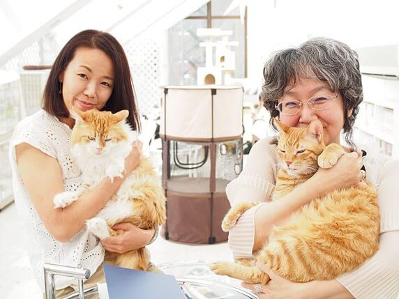 猫を抱いたライター富田さんと東京キャットガーディアン代表の山本さん