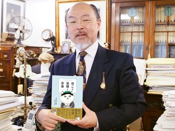 ねこの法律とお金の本を持つ渋谷先生